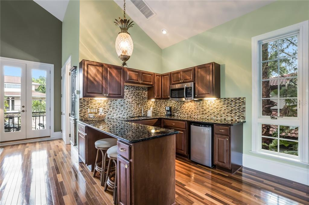 This well appointed carriage house kitchen features granite countertops, tile backsplash, sink, mini-fridge, microwave, and breakfast bar seating. - Single Family Home for sale at 6438 Hollywood Blvd, Sarasota, FL 34231 - MLS Number is A4449895