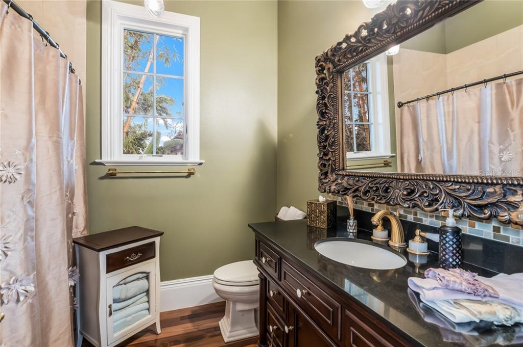 The carriage house features a beautiful bathroom with a large granite-topped vanity and tiled shower. - Single Family Home for sale at 6438 Hollywood Blvd, Sarasota, FL 34231 - MLS Number is A4449895