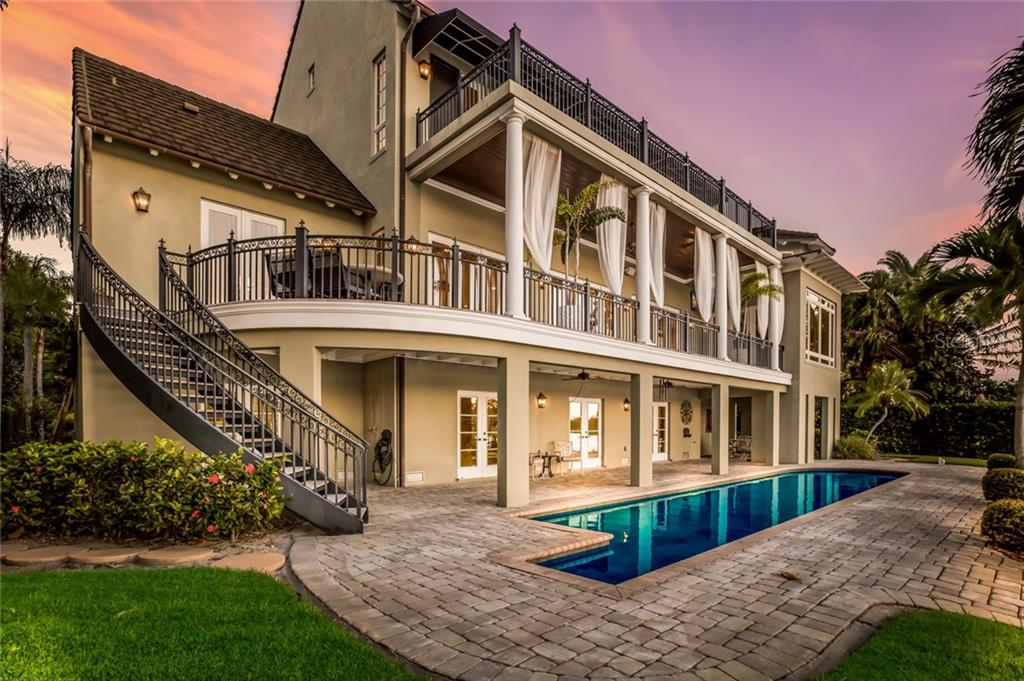 The veranda provides a perfect space for poolside entertaining, with stairs leading to the main floor balcony. - Single Family Home for sale at 6438 Hollywood Blvd, Sarasota, FL 34231 - MLS Number is A4449895