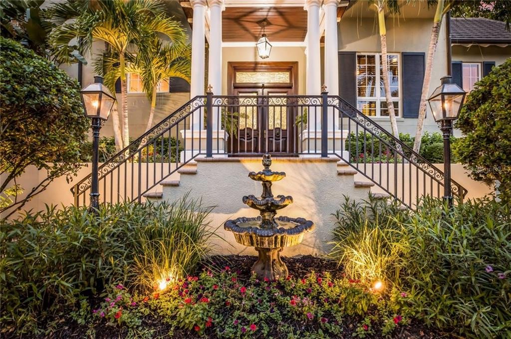 Gas lanterns frame the graceful fountain leading to the main entry as your guests make their way to the custom front doors crafted from African sapele mahogany with leaded glass and transom. - Single Family Home for sale at 6438 Hollywood Blvd, Sarasota, FL 34231 - MLS Number is A4449895