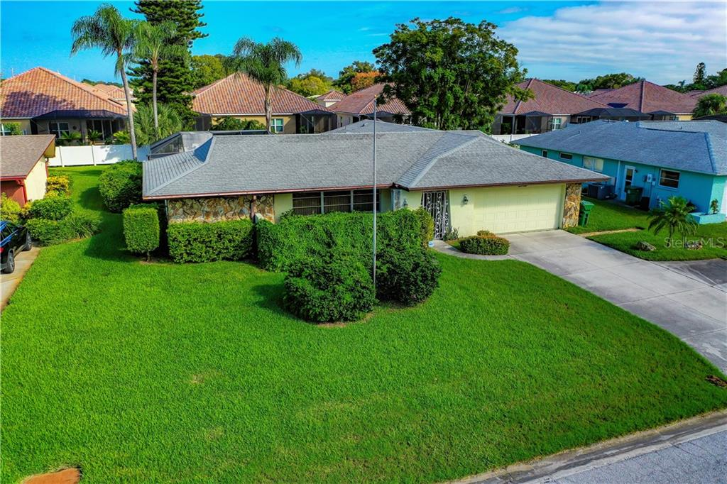 Front of house with lush lawn. - Single Family Home for sale at 7006 18th Ave W, Bradenton, FL 34209 - MLS Number is A4450658