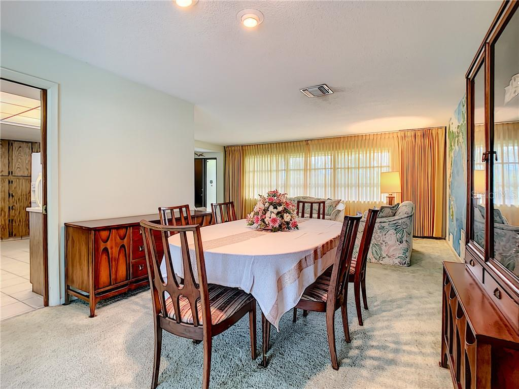 Dining room looking towards front living room and kitchen to the left. - Single Family Home for sale at 7006 18th Ave W, Bradenton, FL 34209 - MLS Number is A4450658