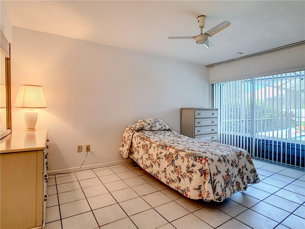Tiled master bedroom looking towards the pool/lanai. - Single Family Home for sale at 7006 18th Ave W, Bradenton, FL 34209 - MLS Number is A4450658