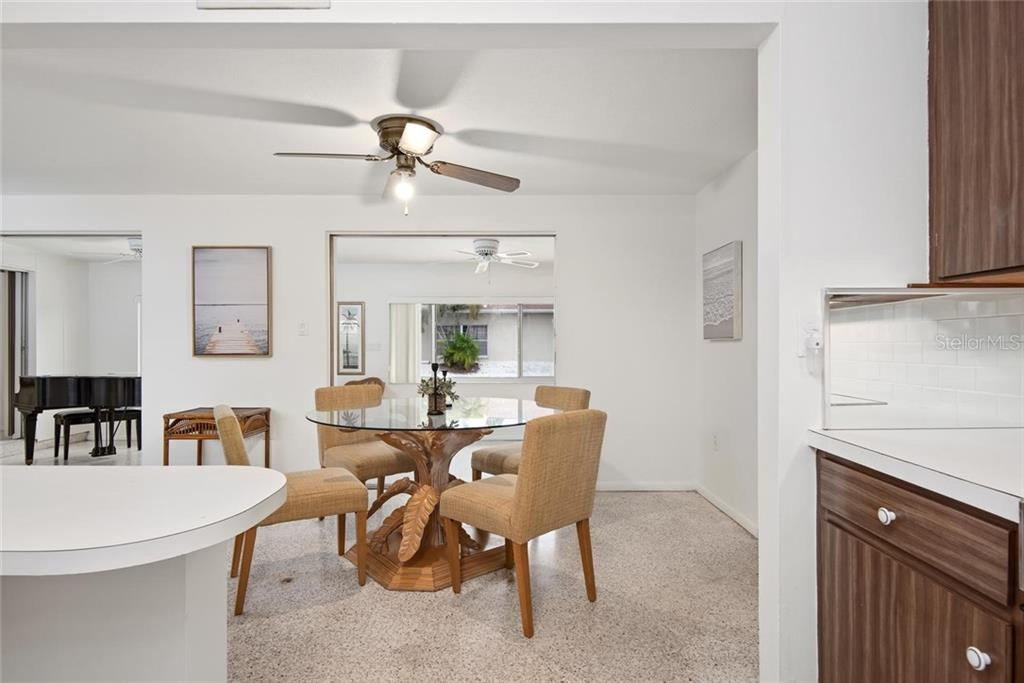 The enclosed Florida room offers a large space for entertaining, overlooking the water outside the large windows. - Single Family Home for sale at 691 Tarawitt Dr, Longboat Key, FL 34228 - MLS Number is A4451584