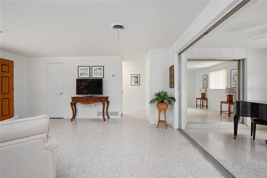 From the master bedroom into the Florida room and the living/dining area beyond. - Single Family Home for sale at 691 Tarawitt Dr, Longboat Key, FL 34228 - MLS Number is A4451584