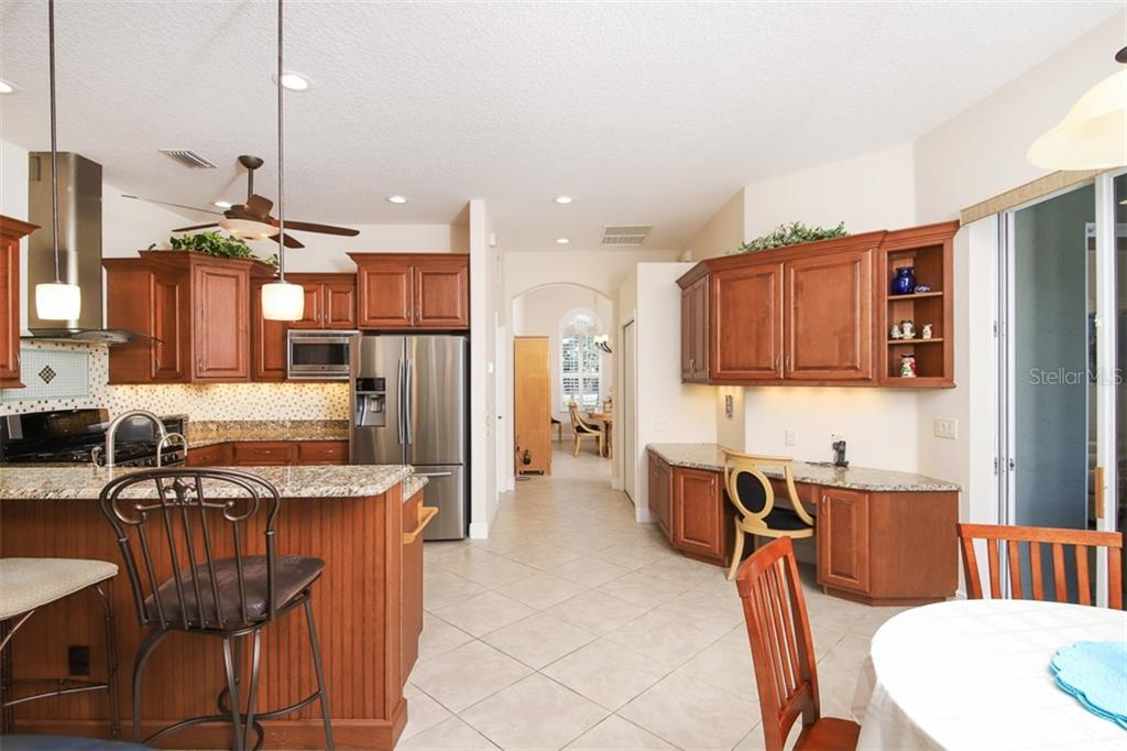 Kitchen, granite counter tops, beautiful cabinets and even a built-in desk - Single Family Home for sale at 6229 Yellow Wood Pl, Sarasota, FL 34241 - MLS Number is A4457471