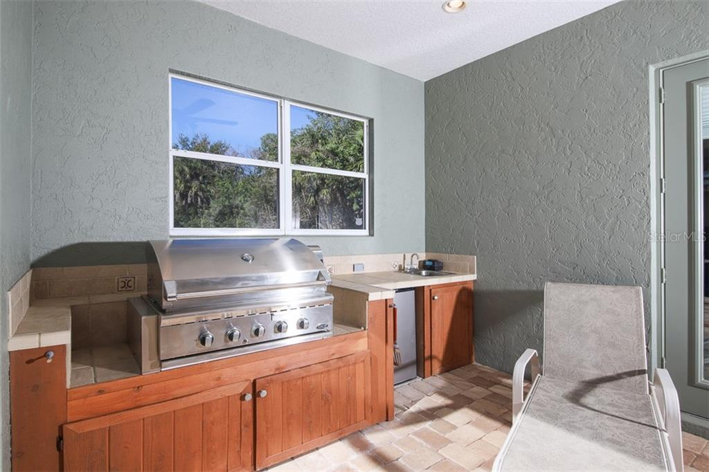 Beautiful covered outdoor kitchen with gas grill, refrigerator and sink in pool caged area - Single Family Home for sale at 6229 Yellow Wood Pl, Sarasota, FL 34241 - MLS Number is A4457471