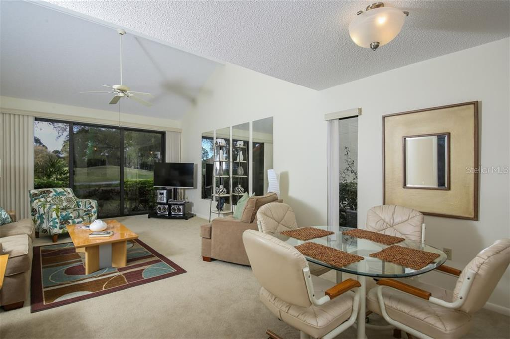 Broad view of great room from entry.  A wall of sliders and vaulted ceiling highlight this beautifully decorated space. - Townhouse for sale at 5319 Huntingwood Ct #51, Sarasota, FL 34235 - MLS Number is A4460231