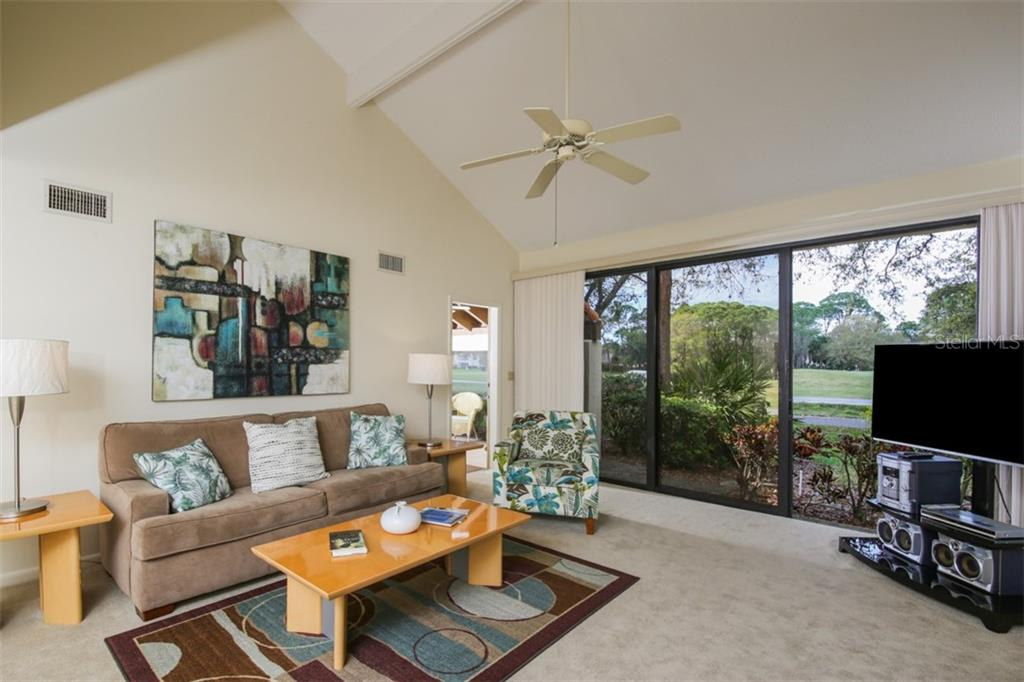 Delightful decor, new large flat screen TV and sound system round out this living room.  Door to lanai connects these two flexible living spaces. - Townhouse for sale at 5319 Huntingwood Ct #51, Sarasota, FL 34235 - MLS Number is A4460231