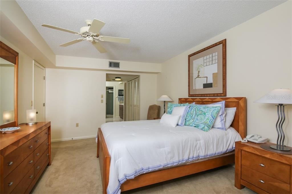 Master bedroom showing hallway with three closets and updated en suite bathroom. - Townhouse for sale at 5319 Huntingwood Ct #51, Sarasota, FL 34235 - MLS Number is A4460231