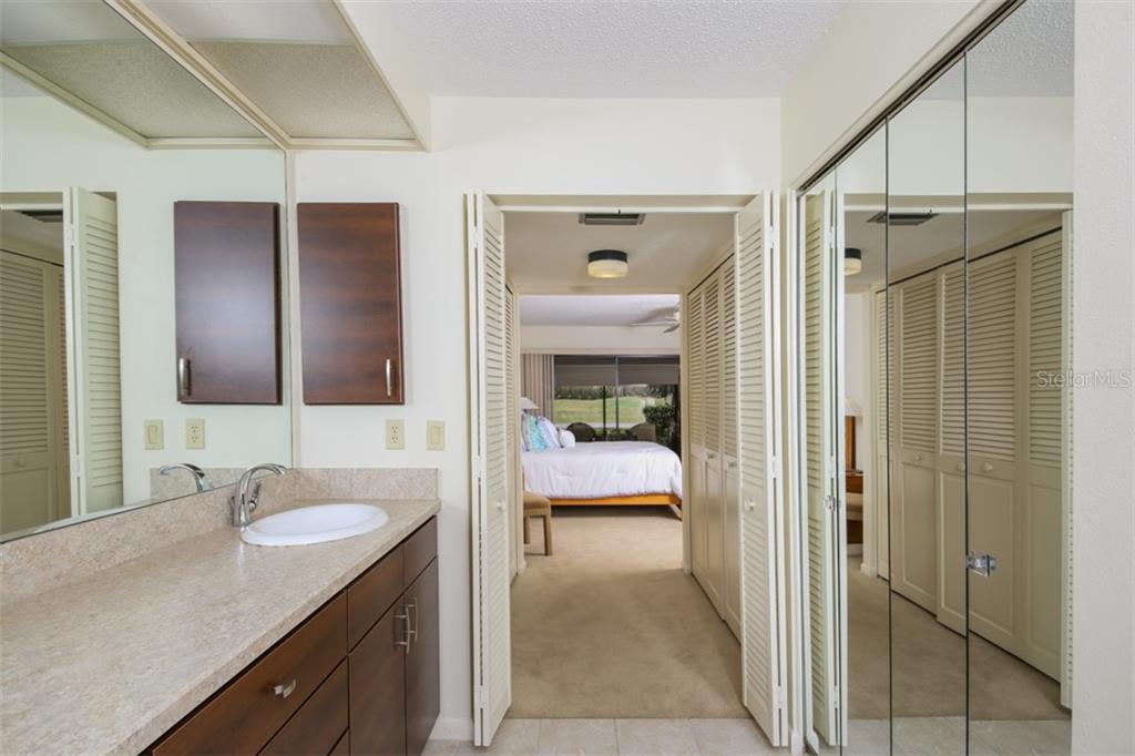 New wood double vanity and view down hall with closets to master bedroom from en suite bathroom. - Townhouse for sale at 5319 Huntingwood Ct #51, Sarasota, FL 34235 - MLS Number is A4460231