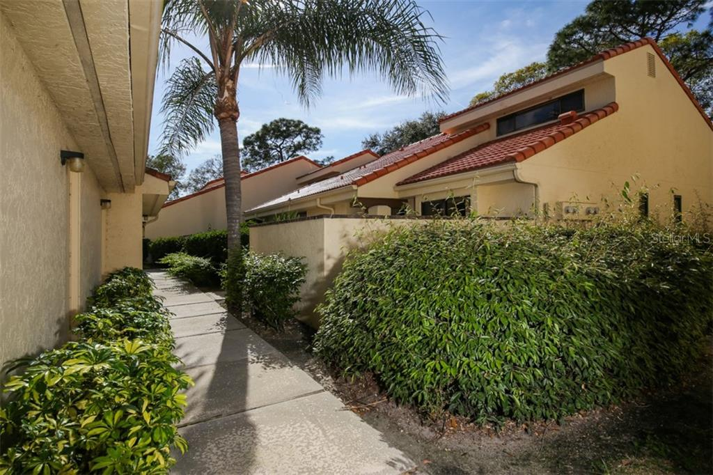 Sidewalk to the walled, private courtyard on right, your garage is the first door on the left. - Townhouse for sale at 5319 Huntingwood Ct #51, Sarasota, FL 34235 - MLS Number is A4460231
