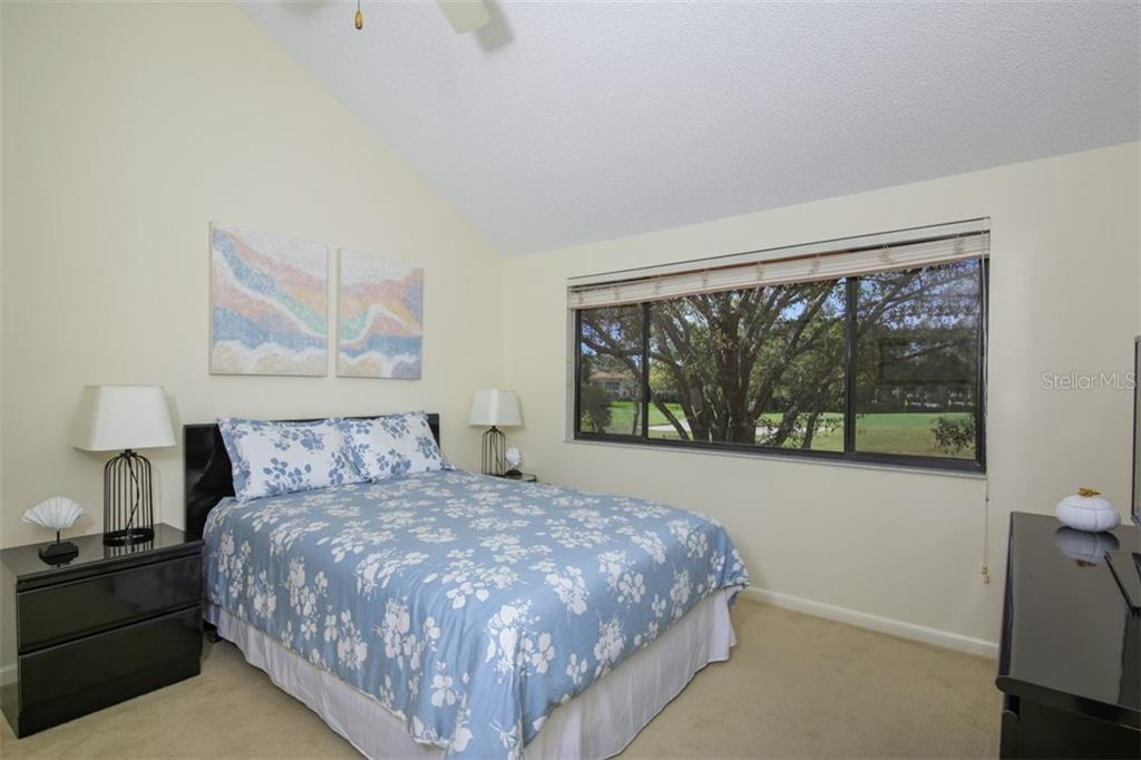 Second guest bedroom upstairs with queen bed, flat screen TV and long golf course and water views. - Townhouse for sale at 5319 Huntingwood Ct #51, Sarasota, FL 34235 - MLS Number is A4460231