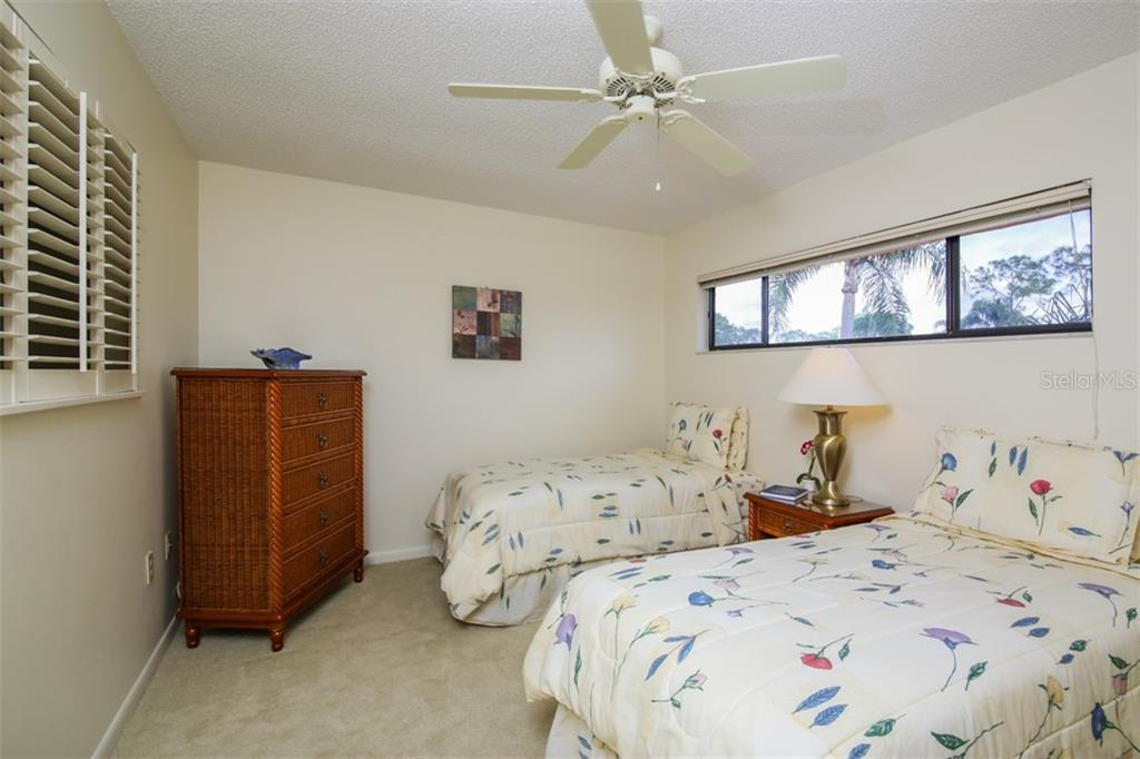 Third guest bedroom with two full beds and views of towering palm trees. - Townhouse for sale at 5319 Huntingwood Ct #51, Sarasota, FL 34235 - MLS Number is A4460231