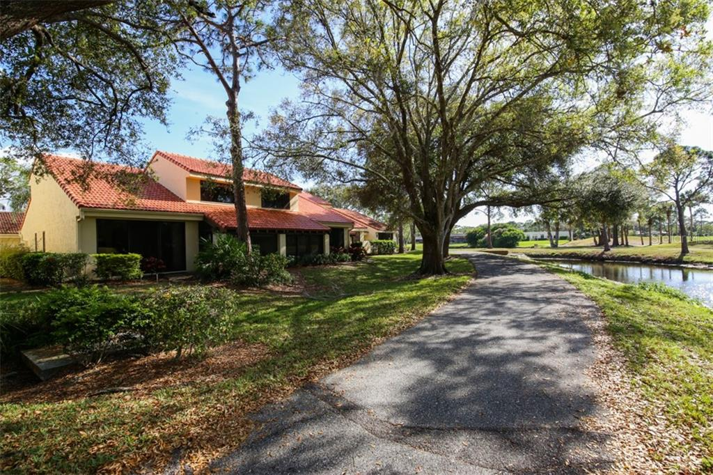 View of meandering path along back of town home with long water views from living room and lanai. - Townhouse for sale at 5319 Huntingwood Ct #51, Sarasota, FL 34235 - MLS Number is A4460231