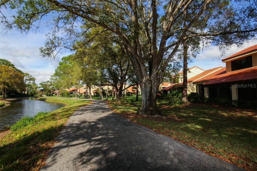 Beautiful Oak trees line the path and waterway and provide lovely shade to the town home on warm days. - Townhouse for sale at 5319 Huntingwood Ct #51, Sarasota, FL 34235 - MLS Number is A4460231