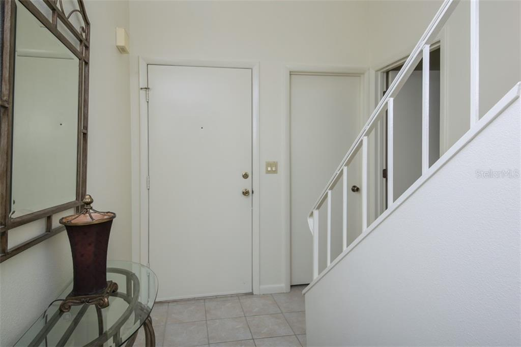 The tiled entry leads to the laundry room (middle door) as well as a guest entrance to the master on the far right. - Townhouse for sale at 5319 Huntingwood Ct #51, Sarasota, FL 34235 - MLS Number is A4460231
