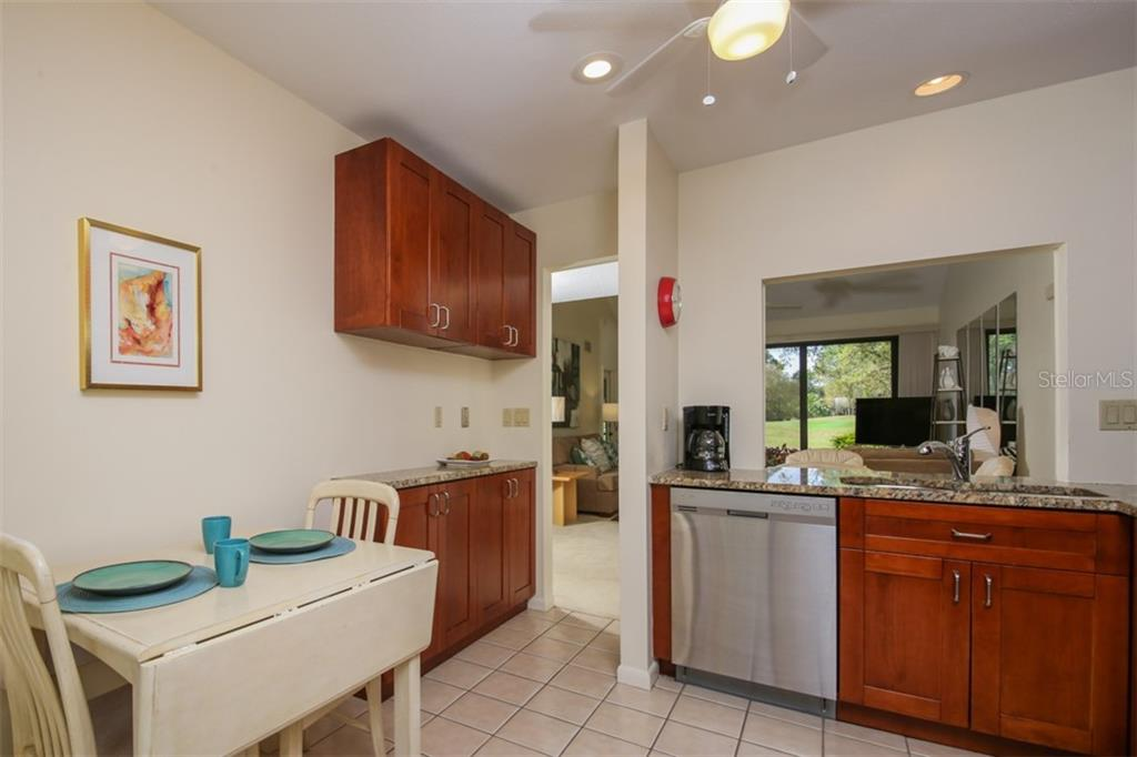 Kitchen with eat in area and custom built in buffet.  Pass through has views of golf course through the great room. - Townhouse for sale at 5319 Huntingwood Ct #51, Sarasota, FL 34235 - MLS Number is A4460231