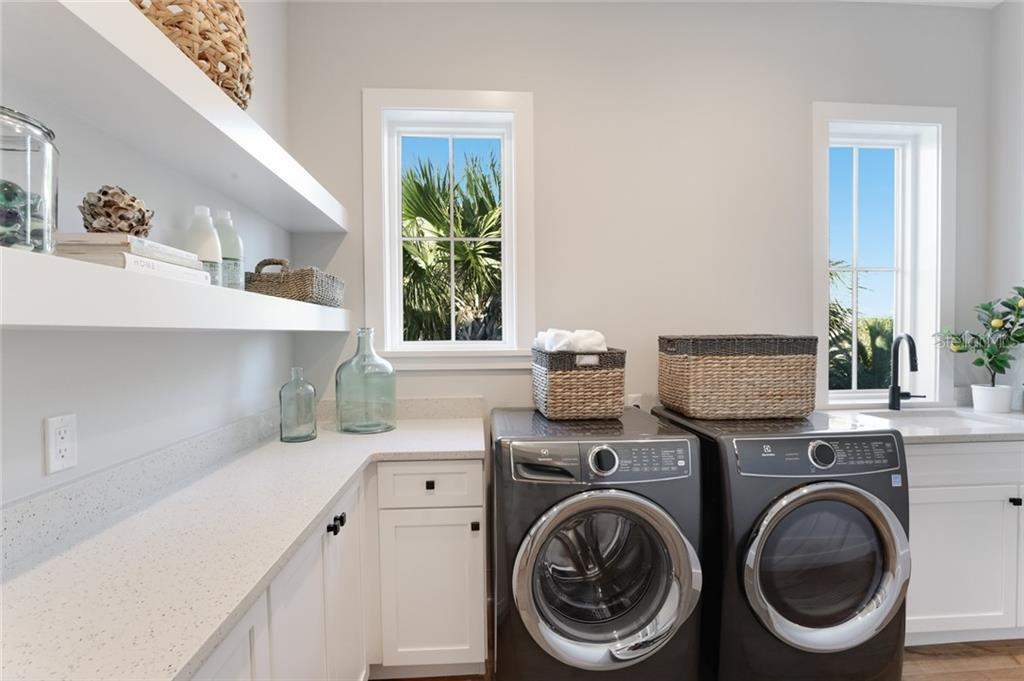 Large laundry room with plenty of storage, utility sink and quartz counters for folding clothes! - Single Family Home for sale at 217 Willow Ave, Anna Maria, FL 34216 - MLS Number is A4466825
