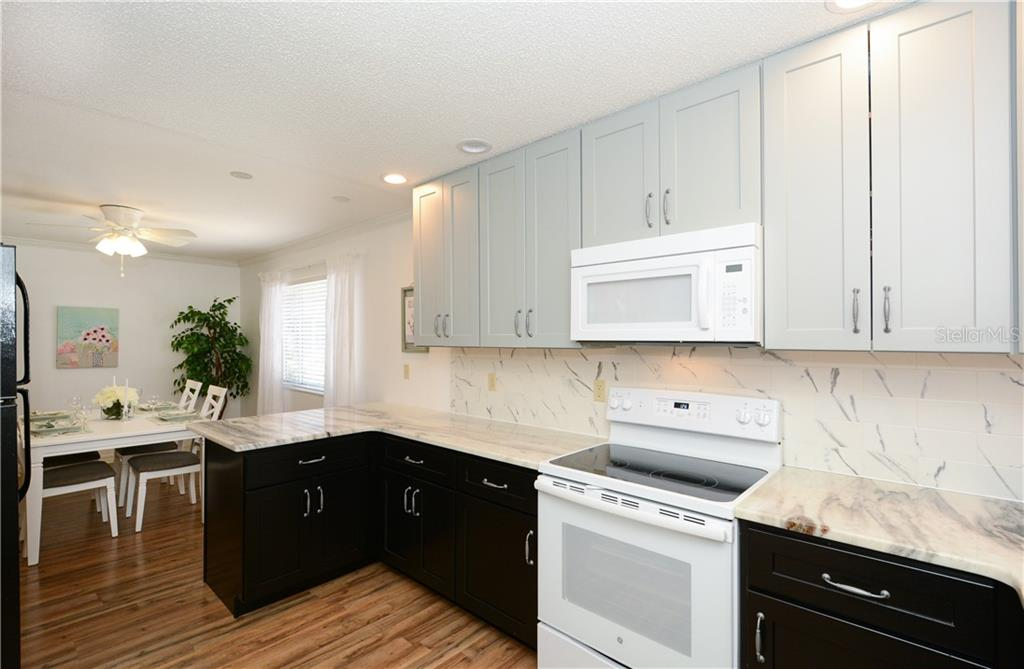 Kitchen with wood cabinetry, stone countertops, new G.E. appliances - Villa for sale at 1321 Glen Oaks Dr E #132, Sarasota, FL 34232 - MLS Number is A4474656