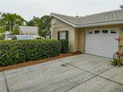 Garage with driveway for parking. - Condo for sale at 115 Woodbridge Dr #104, Venice, FL 34293 - MLS Number is N6108875